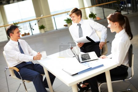 Photo for Young office workers talking with each other during break - Royalty Free Image