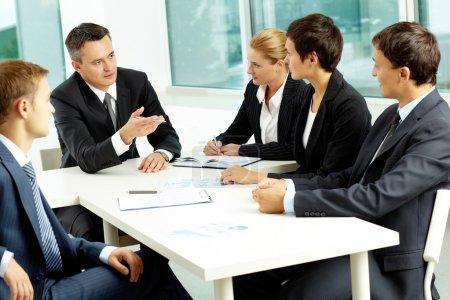 Photo pour Image de collègues confiants regardant leur patron à la réunion - image libre de droit