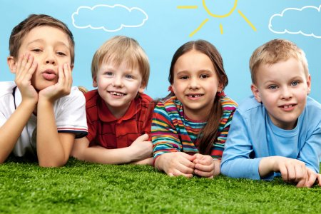 Photo for Group of happy children lying on a green grass - Royalty Free Image