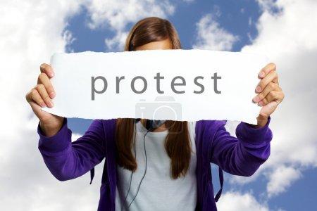 Photo pour Image d'adolescente dans des vêtements décontractés, exprimant la protestation avec feuille de papier - image libre de droit