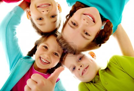 Photo for Photo of joyful children touching by their heads with girl her thumb up - Royalty Free Image
