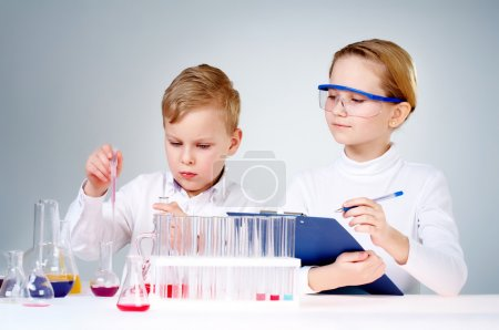 Photo for A little boy mixing chemical liquids and his assistant making notes - Royalty Free Image