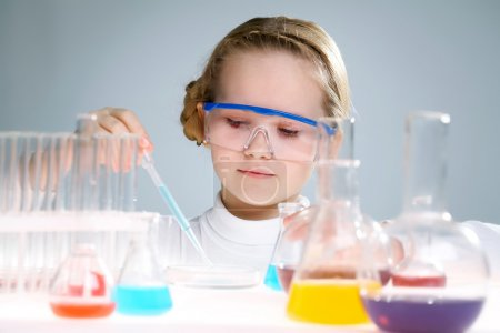 Photo for A little girl analyzing chemical liquid - Royalty Free Image