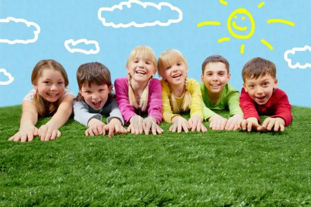 Photo for Group of happy children lying on a grass and stretching their hands - Royalty Free Image