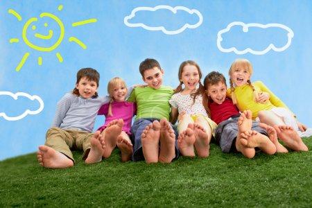 Photo pour Groupe d'enfants heureux se détendre sur l'herbe ensemble - image libre de droit