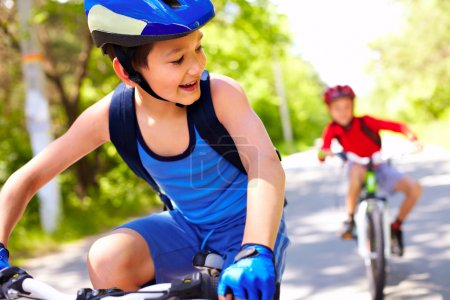 Photo for Two little boys riding bikes one after another - Royalty Free Image