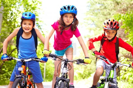 Photo for Portrait of three little cyclists riding their bikes - Royalty Free Image