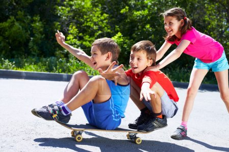 Photo for A girl pushing skateboard with two boys sitting on it - Royalty Free Image