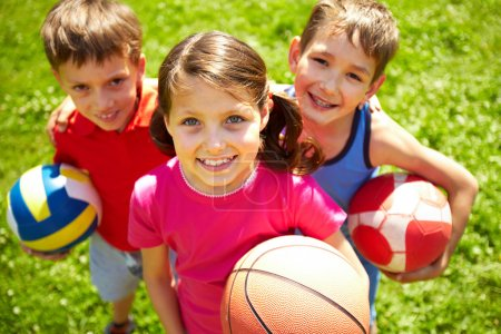 Photo for Portrait of three little children with balls looking at camera and smiling - Royalty Free Image