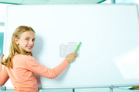 Photo for Portrait of smart schoolgirl by the whiteboard looking at camera - Royalty Free Image