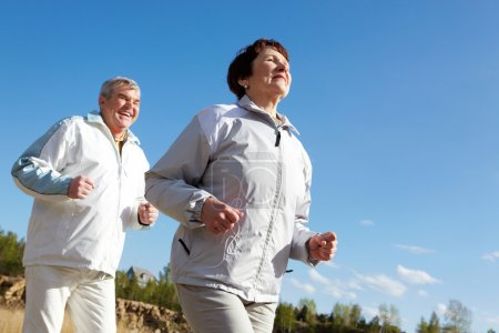 Photo for Portrait of happy mature couple running together - Royalty Free Image