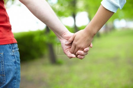 Photo for Close-up of female and male holding by hands in park - Royalty Free Image