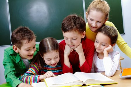 Photo for Portrait of friendly group reading book in classroom - Royalty Free Image