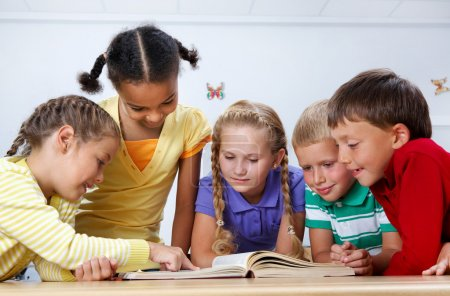 Photo for Portrait of pupils looking at page of encyclopaedia at reading lesson - Royalty Free Image