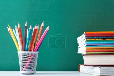 Photo for Image of crayons and exercise books against blackboard - Royalty Free Image