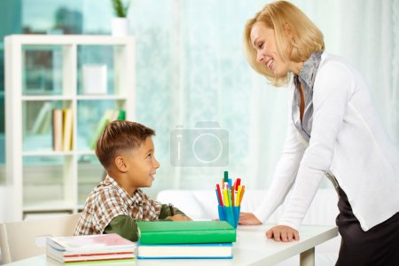 Photo for Portrait of diligent boy drawing at home and his tutor interacting with each other - Royalty Free Image