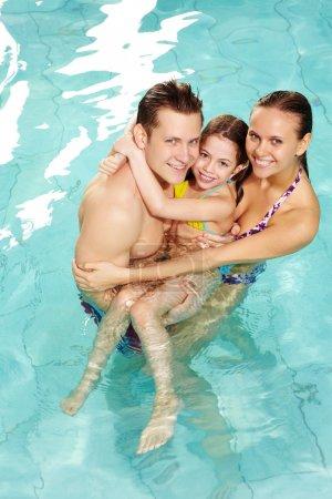 Photo pour Photo de famille heureuse des parents et de la fille cute dans piscine - image libre de droit