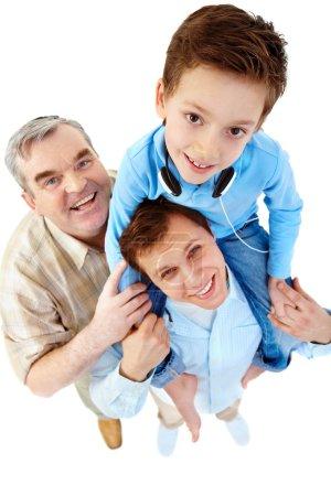 Photo pour Un garçon assis sur les épaules de son père avec un grand-père permanent par eux - image libre de droit