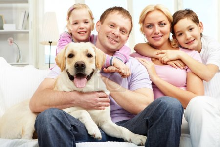 Photo for A happy family of four with a dog sitting on sofa, looking at camera and smiling - Royalty Free Image