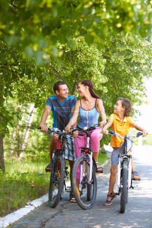 Photo pour Portrait de famille de trois cyclistes en bois - image libre de droit