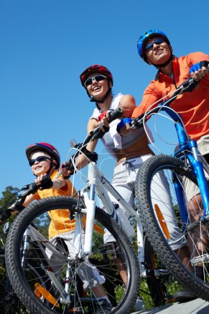 Photo for Portrait of happy family on bicycles against blue sky - Royalty Free Image
