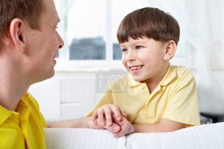 Photo pour Un père et son mignon fils se regardent en parlant - image libre de droit