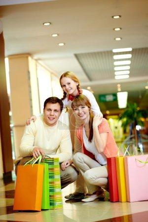 Photo pour Image de famille avec des sacs en papier regardant la caméra dans le centre commercial - image libre de droit
