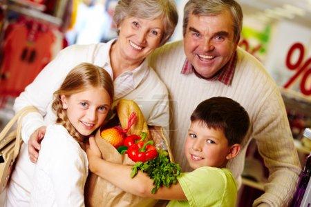 Photo pour Portrait d'heureux grands-parents et petits-enfants holding paquet avec de la nourriture - image libre de droit