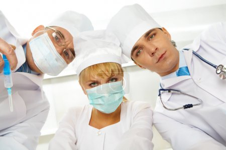 Photo for Three serious therapeutists touching their heads while looking at camera - Royalty Free Image