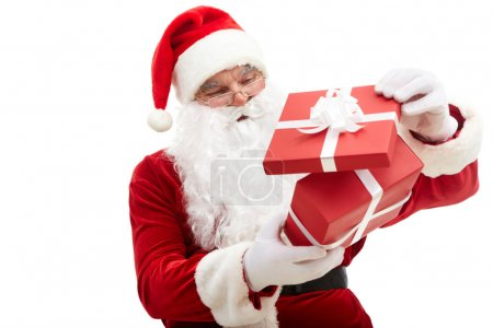 Photo for Photo of happy Santa Claus looking into red giftbox in isolation - Royalty Free Image