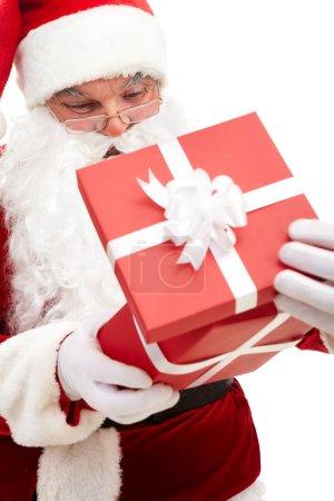 Foto de Foto de Papá Noel feliz mirando en la caja de regalo roja en aislamiento - Imagen libre de derechos