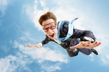 Photo for Conceptual image of young businessman flying with parachute on back - Royalty Free Image