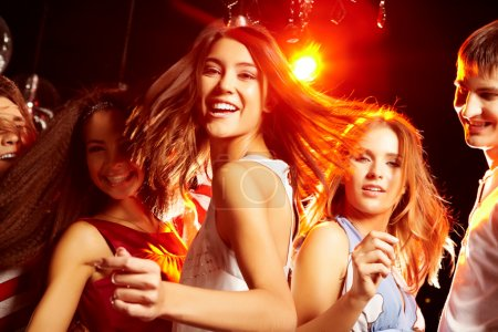Photo for Pretty clubber dancing surrounded by her friends and looking at camera with smile - Royalty Free Image