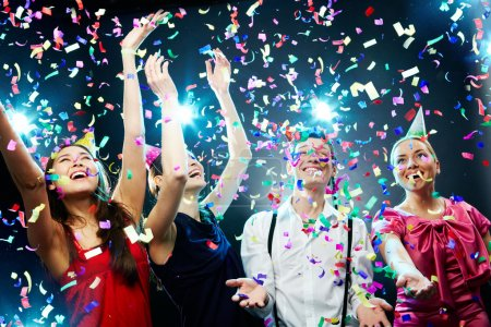 Photo for Four friends making having fun among confetti - Royalty Free Image
