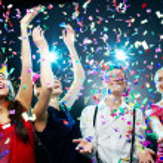 Four friends making having fun among confetti...