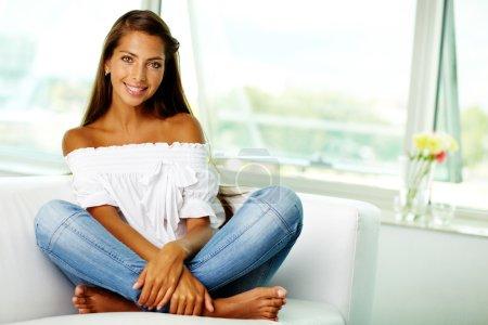Photo pour Portrait de cute brunette assis sur le canapé à la maison - image libre de droit