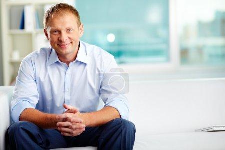 Photo pour Portrait d'un homme confiant assis au bureau - image libre de droit