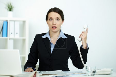 Photo for Portrait of amazed office worker with phone receiver looking at camera - Royalty Free Image