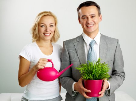 Photo for Photo of happy man with plant and woman holding watering pot looking at camera - Royalty Free Image
