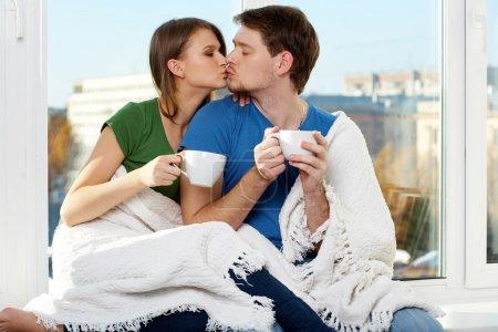 Photo pour Gros plan d'un jeune homme et d'une jeune femme qui touchent ensemble une tasse - image libre de droit