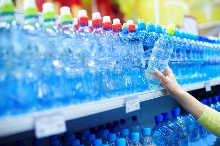 Photo pour Gros plan d'eau de minérale bonne choix féminine dans un magasin - image libre de droit
