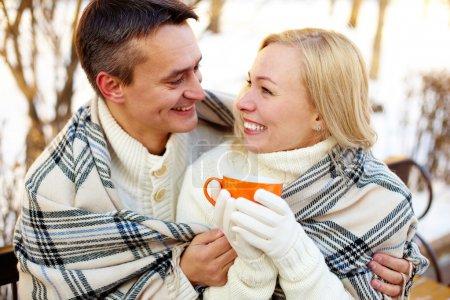 Photo pour Photo de l'homme heureux et jolie femme avec des tasses en plein air en hiver - image libre de droit