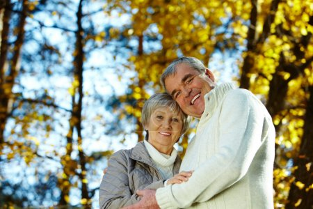 Photo for Photo of amorous aged man and woman looking at camera in autumnal park - Royalty Free Image