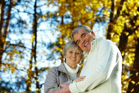 Photo pour Photo d'un homme et d'une femme âgés amoureux regardant une caméra dans un parc automnal - image libre de droit
