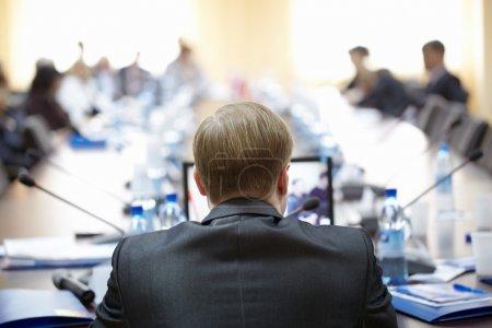 Photo pour Vue arrière du haut-parleur avec ordinateur portable devant lui présentant son rapport au public - image libre de droit