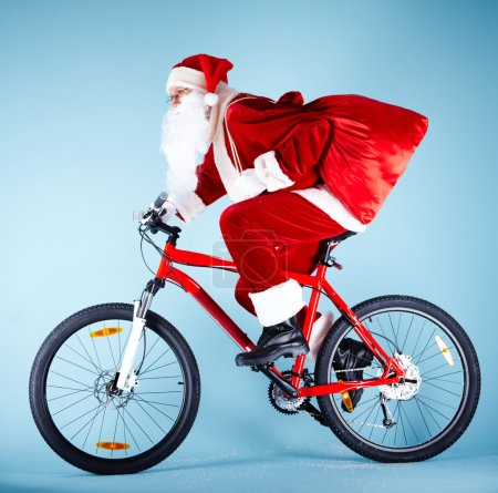 Photo for Photo of Santa Claus with red sack riding bike - Royalty Free Image