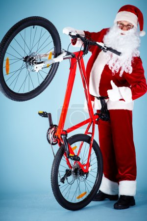 Photo for Photo of happy Santa Claus showing thumb up with his bike near by - Royalty Free Image