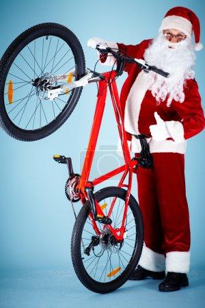 Foto de Foto de Santa Claus feliz mostrando el pulgar hacia arriba con su bicicleta cerca - Imagen libre de derechos