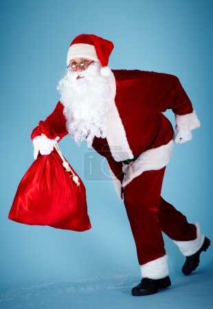 Photo for Photo of happy Santa Claus running with red sack - Royalty Free Image