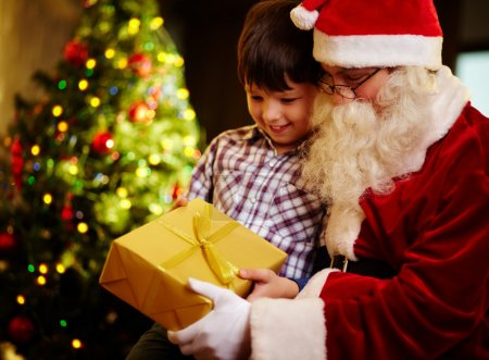 Photo for Photo of cute boy and Santa Claus holding giftbox and looking at it - Royalty Free Image